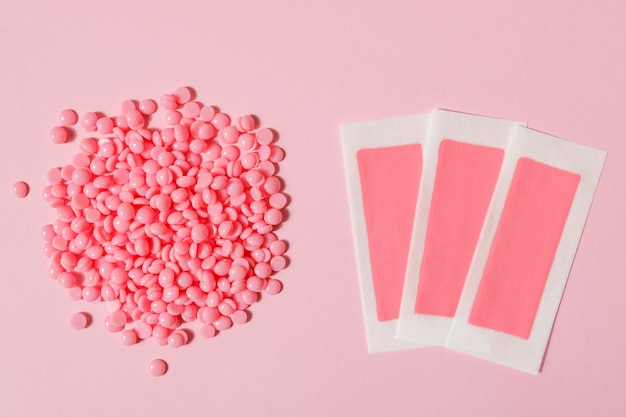 Beautiful pink depilatory wax granules and wax strips for depilation on a pink background