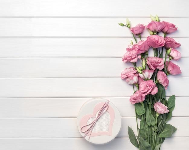 美しいピンクのトルコギキョウの花と白い木製の背景に手作りのギフトボックス。コピースペース、上面図、