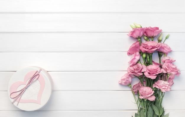 美しいピンクのトルコギキョウの花と白い木製のテーブル、上面図の手作りギフトボックス
