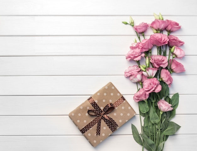 Beautiful pink eustoma flowers and handmade gift box on white wooden background. copy space, top view,