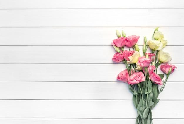 白い木製の背景に美しいピンクのトルコギキョウの花。コピースペース、上面図、