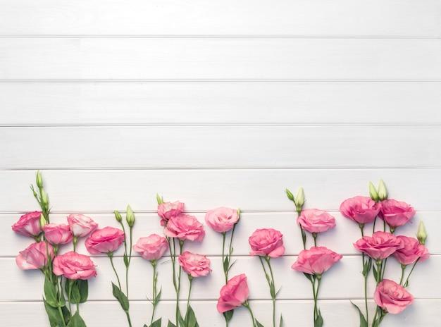 Красивые розовые цветы эустомы на белом фоне деревянных. копировать пространство, вид сверху,