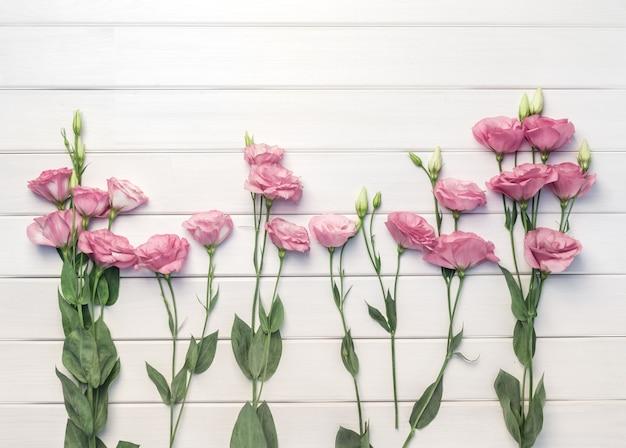 白い木製のテーブル、上面図の美しいピンクのトルコギキョウの花