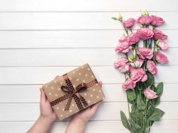 Beautiful pink eustoma flowers and woman hands holds handmade gift box on white wooden background. copy space, top view,