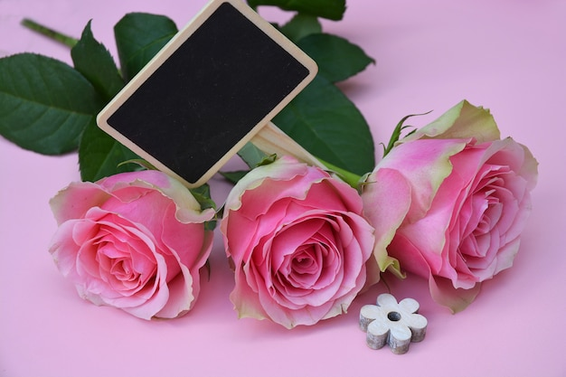 Beautiful pink flowers with a wooden shaped flower on a pink surface