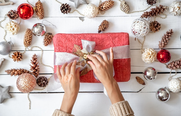 Beautiful pink gift box in hands against the background of details of christmas decor close up.