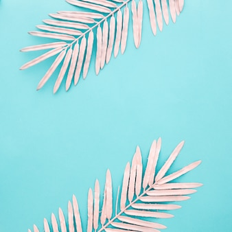 Beautiful pink leaves on light blue background with copyspace