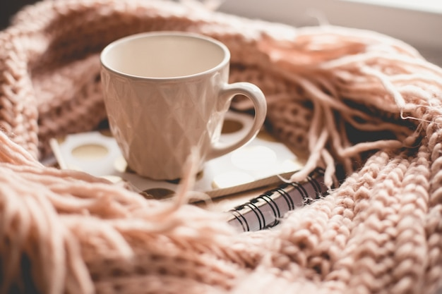 Beautiful pink mug of tea with notebook and knitted scarf
