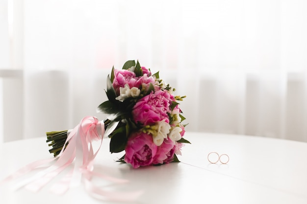 Beautiful pink peonies bouquet  and wedding rings lie on a white table.