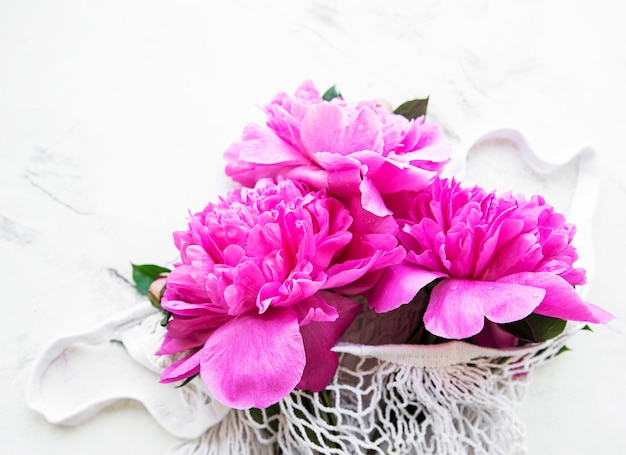 Beautiful pink peonies in a fashionable string bag on a white marble surface