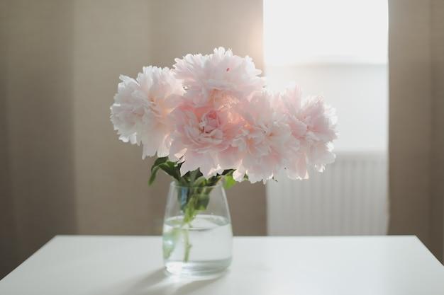 Красивые розовые пионы в стеклянной вазе на белом столе у окна