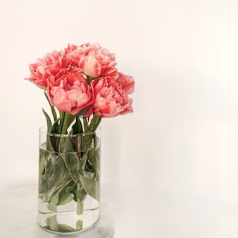 Beautiful pink peony flowers bouquet in glass vase on marble table on white. beauty floral composition