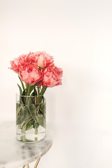 Beautiful pink peony flowers bouquet in glass vase on marble table on white.