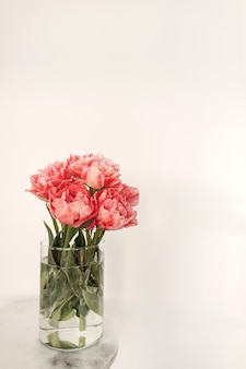 흰색 대리석 테이블에 유리 꽃병에 아름 다운 분홍색 모란 꽃 꽃다발. 최소한의 인테리어 디자인 장식