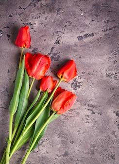 灰色の質感のあるコンクリートの背景に美しいピンクレッドのチューリップの花束。