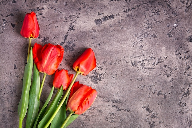 Beautiful pink-red bouquet of tulips on a gray, , concrete background. event design concept, valentines day, mothers day, flat lay and copy space