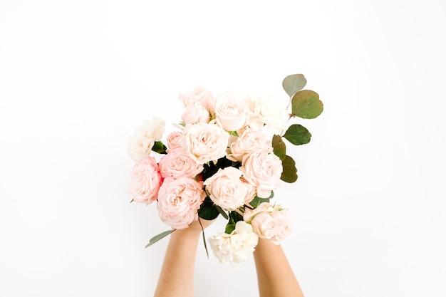 白い背景で隔離の女の子の手で美しいピンクのバラの花とユーカリの花束。フラットレイ、トップビュー