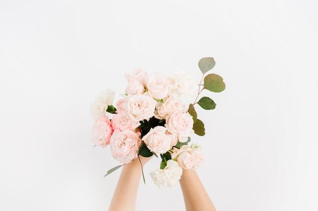 白い背景で隔離の女の子の手で美しいピンクのバラの花とユーカリの枝の花束