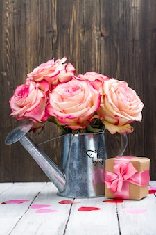Beautiful pink rose in a tin watering can on wood