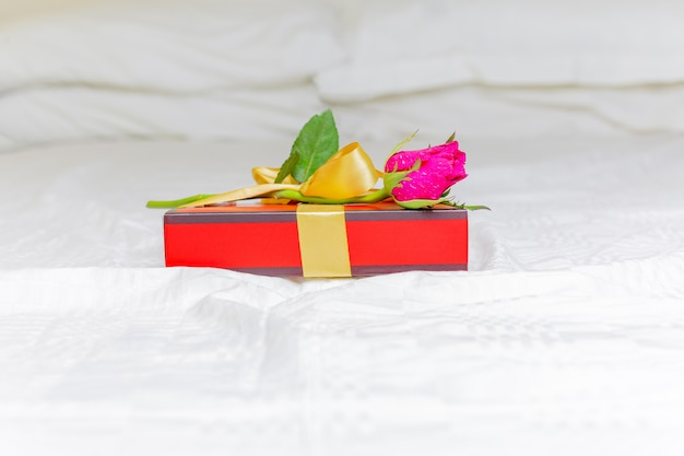 Beautiful pink rose with a gift box on the bed valentines day concept.