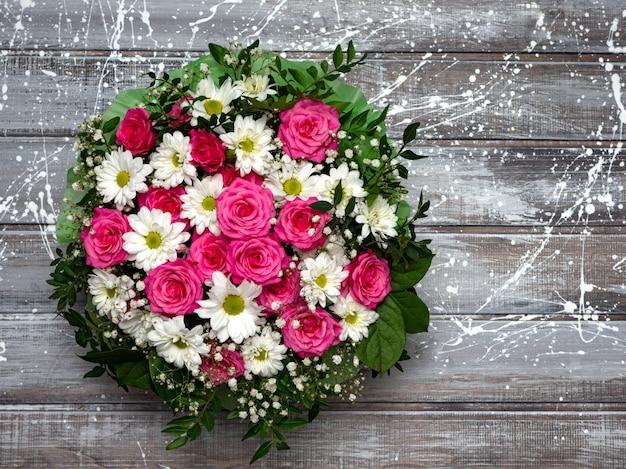 Красивые розовые розы и белые ромашки в коробке на сером деревянном фоне.
