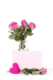 Beautiful pink roses in a bottle on white