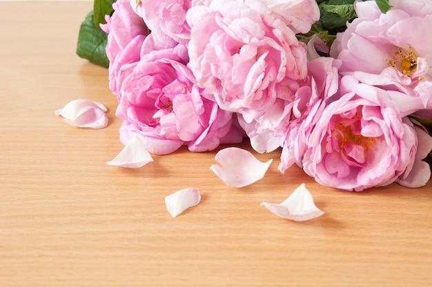木製のテーブルの上に花びらと美しいピンクのバラの束