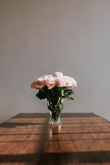 Красивые розовые розы в вазе на столе