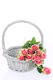 白い背景の上のバスケットの美しいピンクのバラ