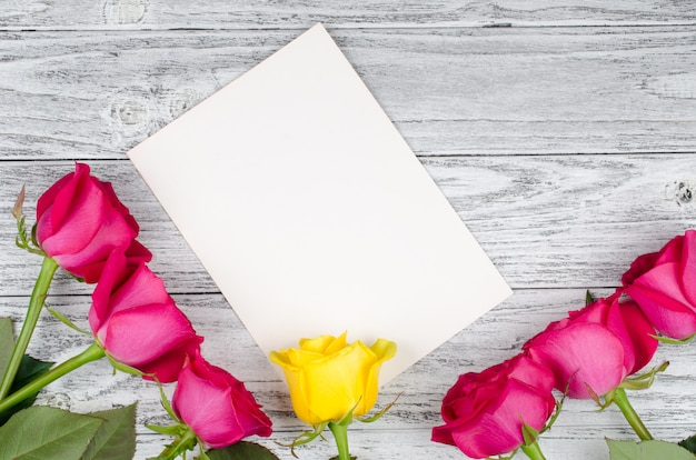 Beautiful pink roses and a single yellow rose on a blank white greeting card against a worn wooden background