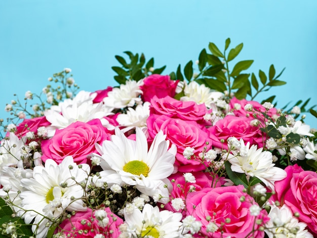 Beautiful pink roses and white daisies in a box on a blue background.