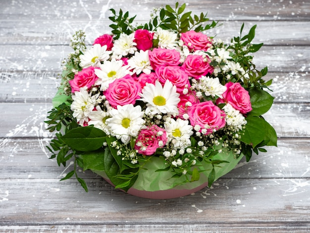 Beautiful pink roses and white daisies in a box on a gray wooden background.