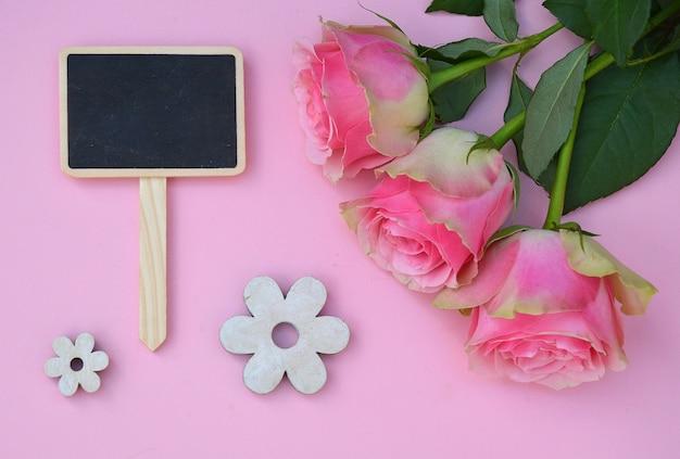 Belle rose rosa con fiorellini in legno a forma di isolato su uno sfondo rosa