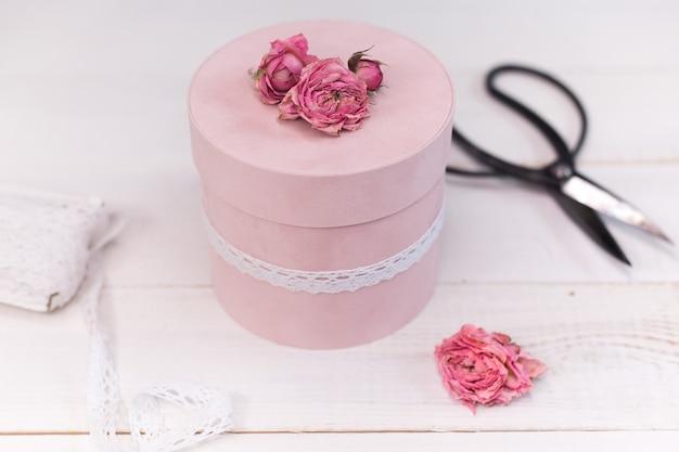 Красивая розовая круглая подарочная упаковка декорирована зауженными розочками.