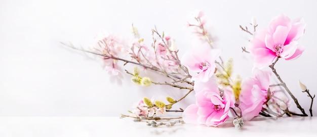 Красивая розовая весенняя цветочная композиция над белой. цветы магнолии, цветущие ветви вишни и ивы.