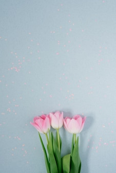 Beautiful pink spring tulips on a light blue background with pink sequins lay flat.