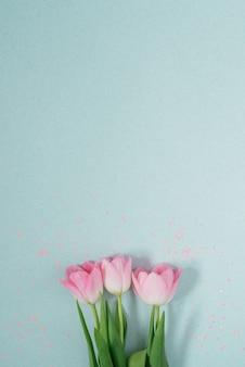 Плоские красивые розовые весенние тюльпаны на светлом мятном фоне с розовыми блестками. копия пространства. валентинка, день рождения, юбилей, 8 марта, пасха