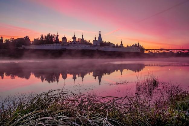 Красивый розовый восход солнца с туманом над рекой успенский собор волга река старица