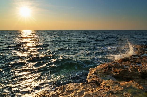 Красивый розовый закат и водные камни над скалистой береговой линией черного моря в крыму в летний день. природный ландшафт фон и обои