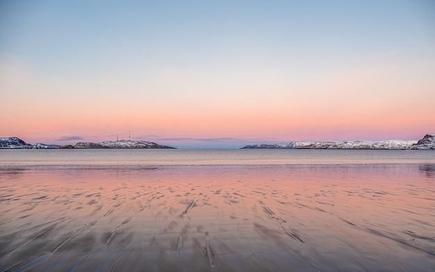 北極海の美しいピンクの夕日。地平線上に雪をかぶった丘のある半島。
