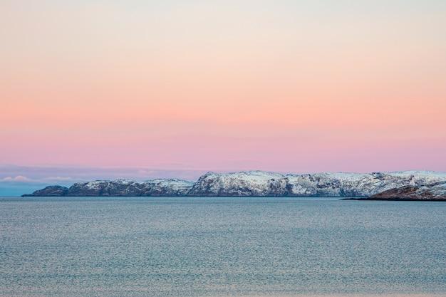 北極海の美しいピンクの夕日地平線に雪をかぶった丘のある半島