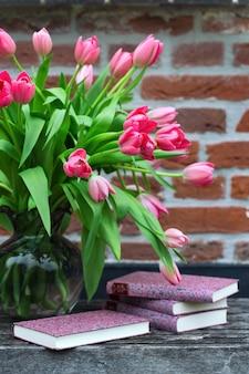 Красивые розовые тюльпаны в вазе и книги на фоне кирпичной стены