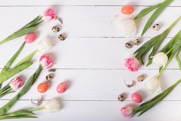 화려한 메 추 라 기 및 닭고기 달걀 흰색 나무 테이블에 둥지에 아름 다운 핑크 튤립. 복사 공간 봄과 부활절 휴가 개념.