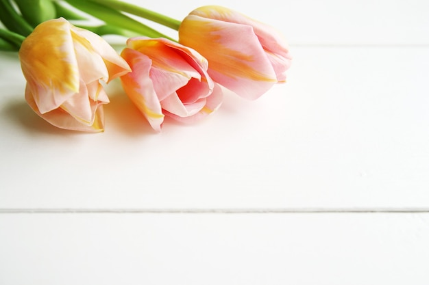 Beautiful pink tulips on wooden background, copy space for text.