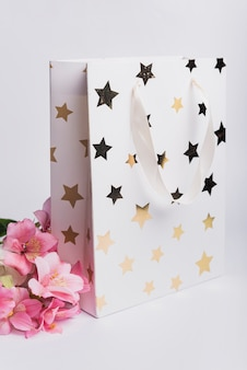 Beautiful pink water lily near the white shopping bag with golden star shape on white background