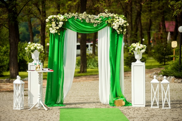 Beautiful place for wedding with arch decorated with flowers in the park.