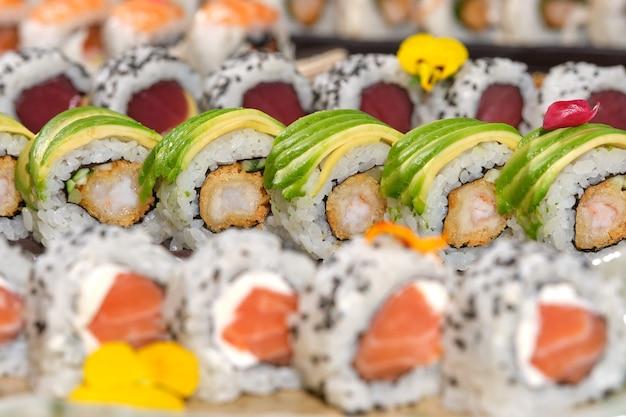 Красивые тарелки вкусных суши на деревянном столе