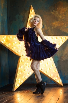 紺色のレースのスカートと輝く星でポーズをとるメッシュストッキングを身に着けている美しい遊び心のある大人のブロンドの女性。舞台で演じる女優。劇場またはダンサー。