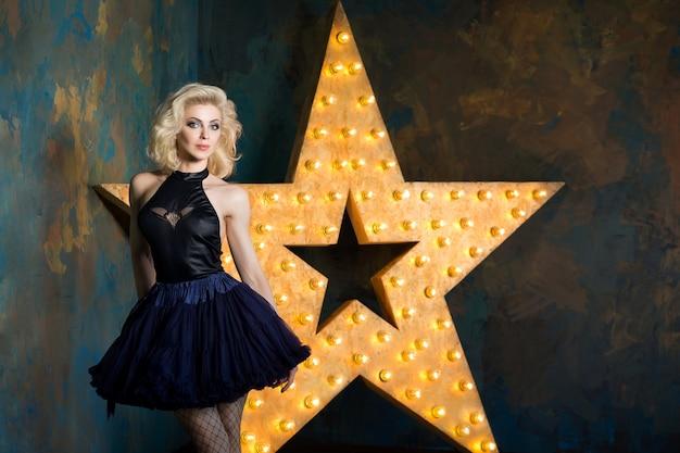 紺色のレースのチュチュスカートとメッシュのストッキングを身に着けている美しい遊び心のある大人のブロンドの女性は、輝く星と暗い壁の上にポーズをとっています。舞台で演じる女優