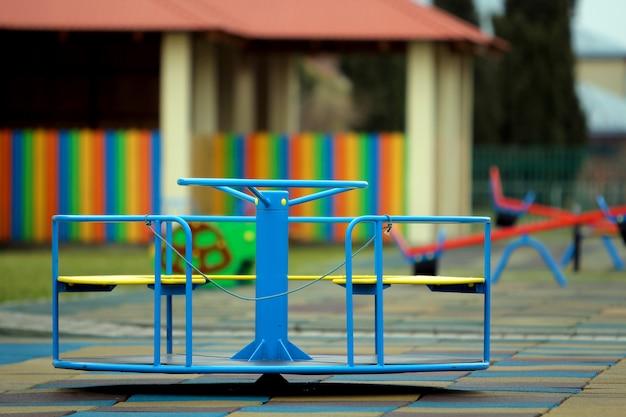 Красивая детская площадка в детском саду с мягким покрытием, яркими качелями, каруселью и скамейкой в солнечный день. идеальное место для активного отдыха детей.